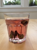 Green cones leach tannins into a glass of water, turning it a lovely shade of red.